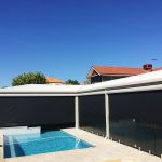 paved pool area and back verandah with outdoor blinds fully down.