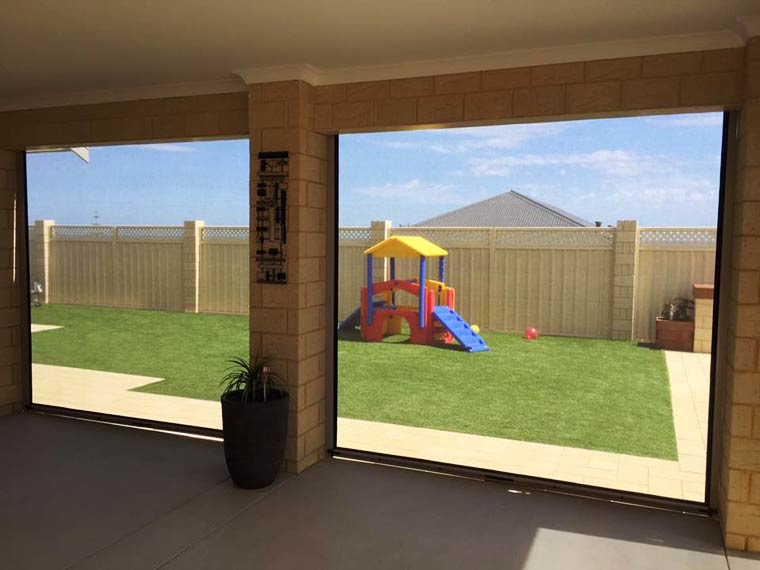 looking through mesh blinds to grass in yard in Jindalee