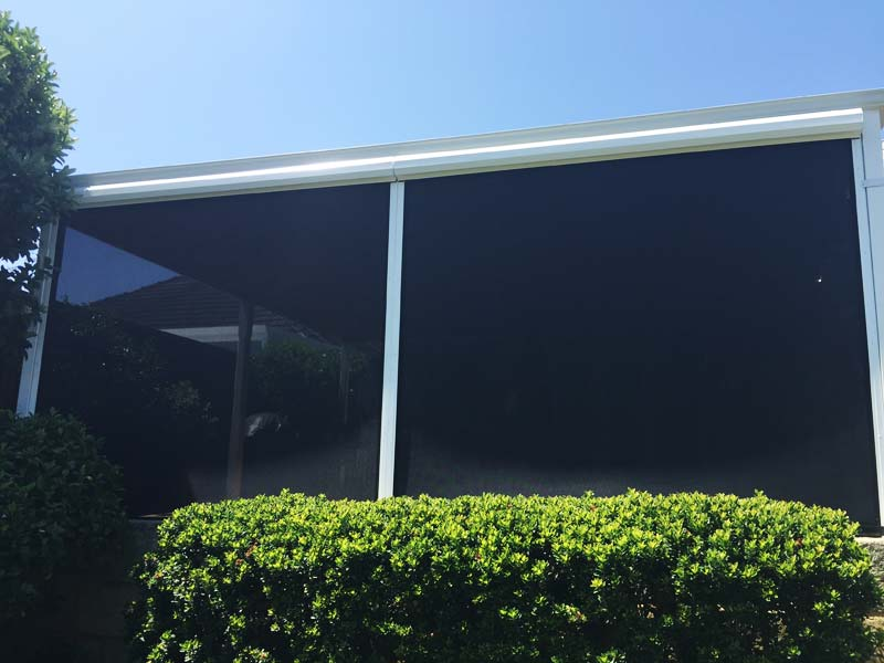 looking up over hedge to back verandah with dark patio blinds installed.