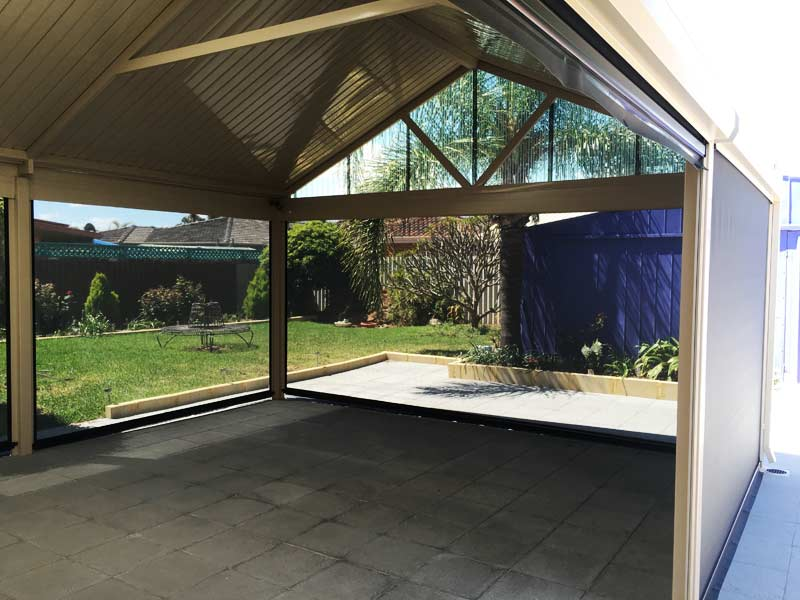 steel patio built on concrete pavers with outdoor blinds installed.