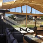 outdoor dining setting in covered area with patio blinds.