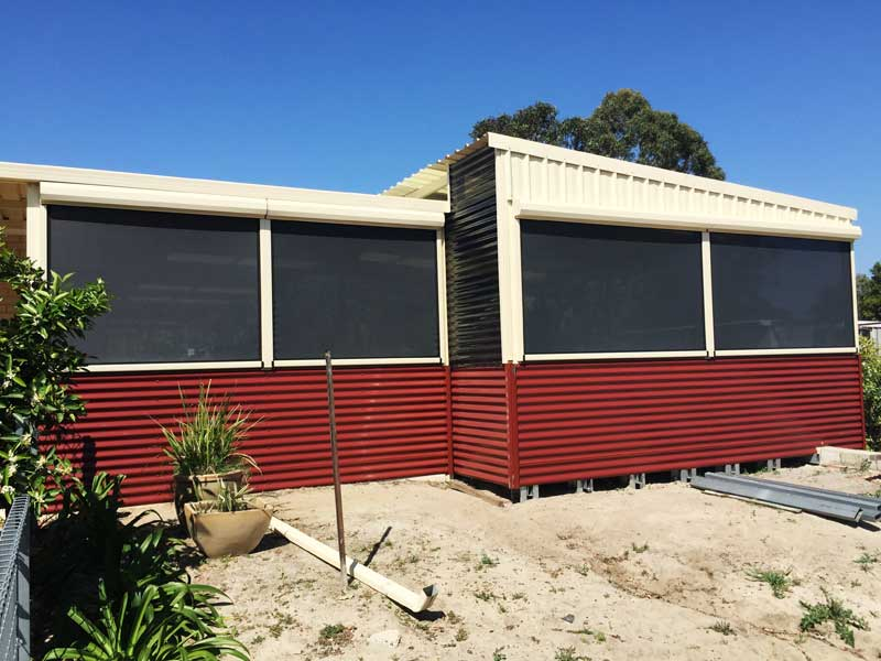 sandy backyard with windows installed with dark shade mesh blinds.