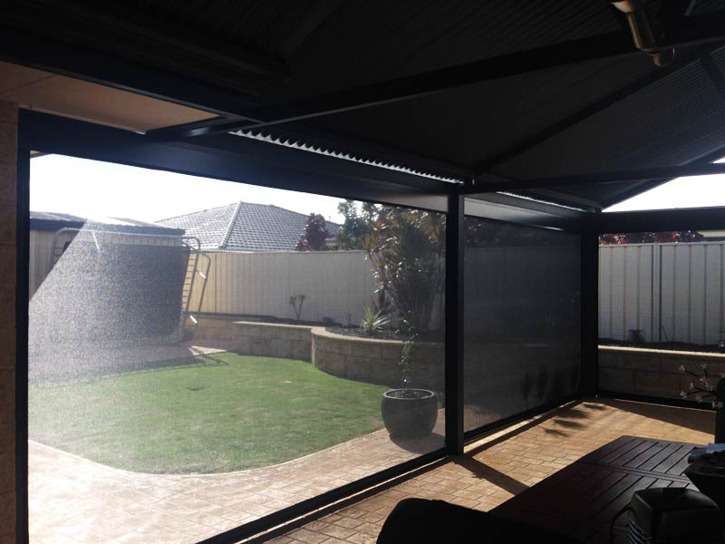 patio looking through ziptrak blinds to yard and upturned trampoline.