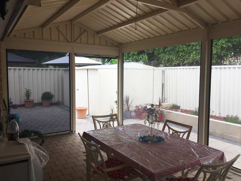 outdoor dining area with dark patio blinds on one side and clear pvc on the other.