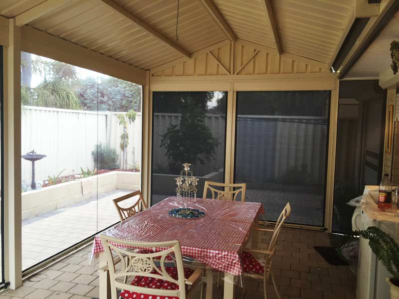 simple outdoor patio area with dining table and blinds.