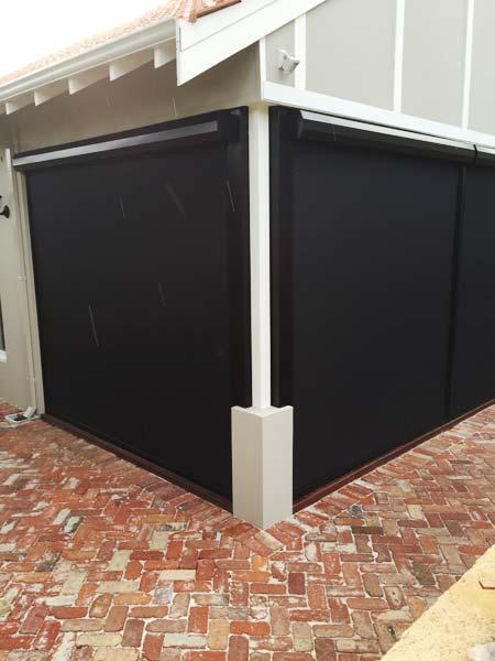 dark shade mesh blinds both drawn down to brick path way