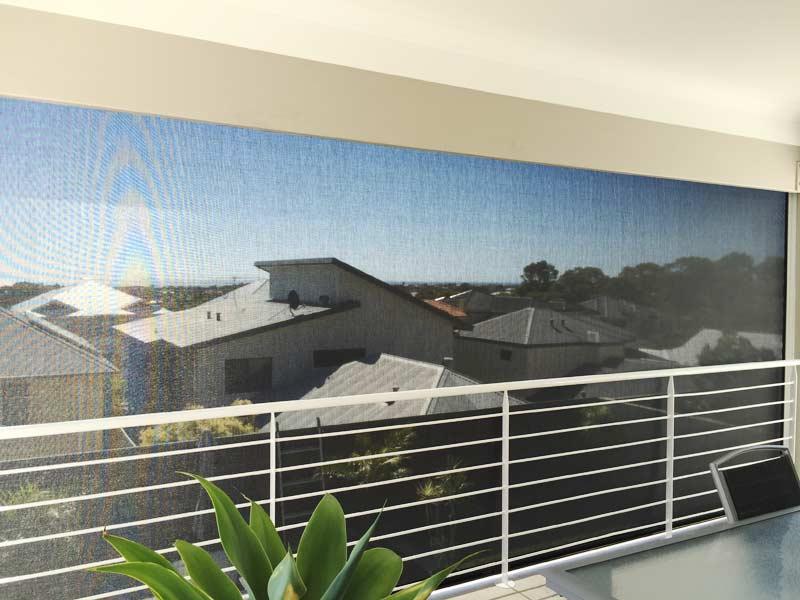 view from balcony over neighbourhood houses through ziptrak blinds