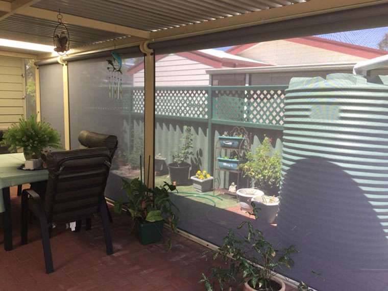 the dark mesh ziptrak blinds still allow a view out to the garden and water tank