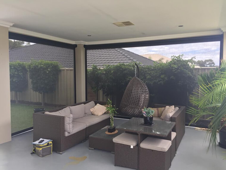 lovely patio furniture setting with ziptrak blinds pulled down