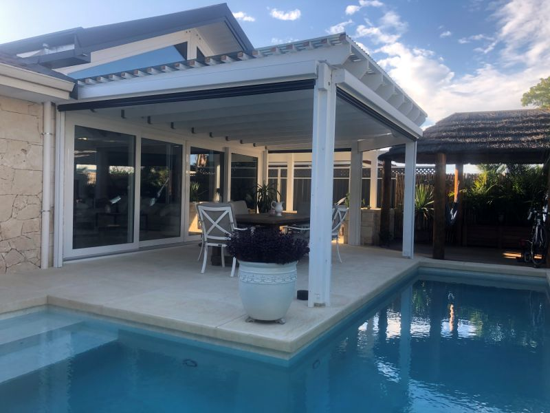 motorised outdoor blinds installation in patio next to swimming pool